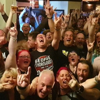 Shot from the band's perspective on stage, the rock crowd at the Pub, Lancaster, cheering and waving their arms. Guitarist Neil has also photo-bombed the picture!