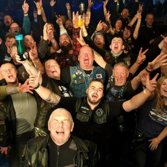 Shot from the band's perspective on stage, a group of bikers smiling, cheering and waving their arms. Guitarist Neil has also photo-bombed the picture!