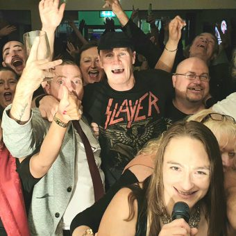 Shot from the band's perspective on stage, the crowd at Y Pentan, Mold, smiling, cheering and waving their arms. Guitarist Neil and singer Ann have also photo-bombed the picture!