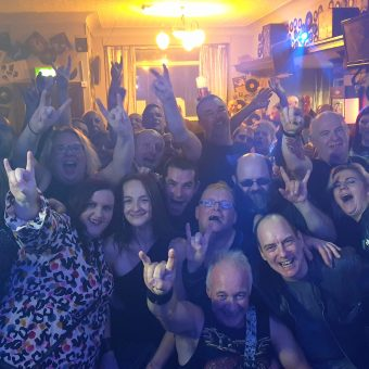Shot from the band's perspective on stage, the crowd at the Bath, Morecambe, smiling, cheering and waving their arms. Guitarist Neil and singer Ann have also photo-bombed the picture!