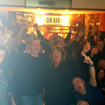 Shot from the band's perspective on stage, the crowd at the Jolly Nailor, Atherton, smiling, cheering and waving their arms.