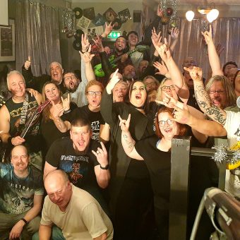 The crowd at the Bath, Morecambe, smiling, cheering and waving their arms. Band members Aaron, Alan, Neil and Pete have also photo-bombed the picture!