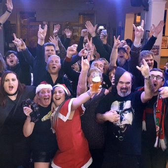 The crowd at Saith Seren, Wrexham, smiling, cheering and waving their arms. Band members Aaron, Neil and Alan have also photo-bombed the picture!