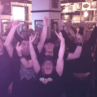 The crowd at the Pub, Lancaster, smiling, cheering and waving their arms.