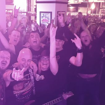 The crowd at the Pub, Lancaster, smiling, cheering and waving their arms. Guitarist Neil has also photo-bombed the picture!