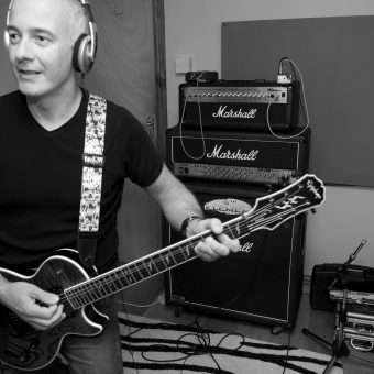 Neil playing guitar at the studio, black and white.