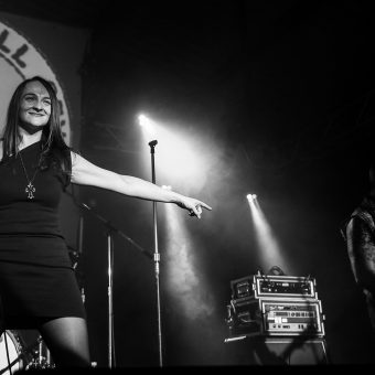 Ann holding her mic and smiling, pointing at Alan as he plays a solo. Black and white.