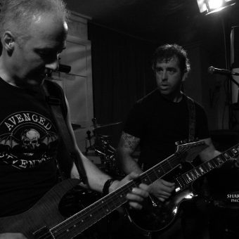 Neil and Alan playing guitar, black and white.