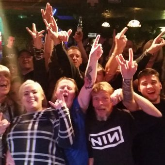 The crowd at Bootleggers Bar, Kendal, cheering and waving their arms.