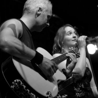 Neil playing acoustic guitar, Ann singing.