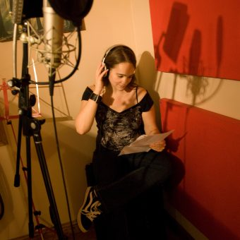 Ann reading some music with a microphone in the foreground.