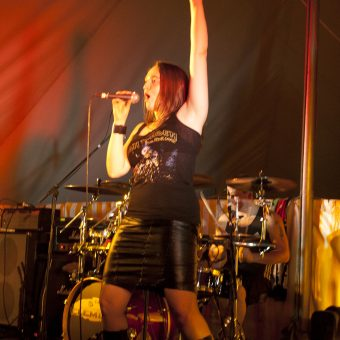 Ann singing and raising her left hand to give the sign of the horns.