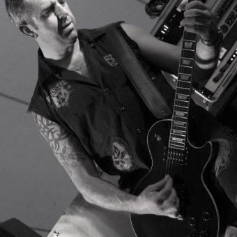 Alan playing guitar, black and white.