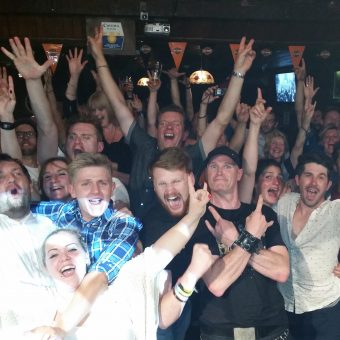 The crowd at Bootleggers Bar, Kendal, cheering and waving their arms. A man (Colin) stands in the centre giving the sign of the horns with his arms crossed.
