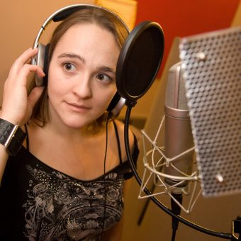 Ann with a microphone at the studio.