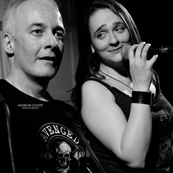 Ann smiling at Neil as she holds the mic, black and white.