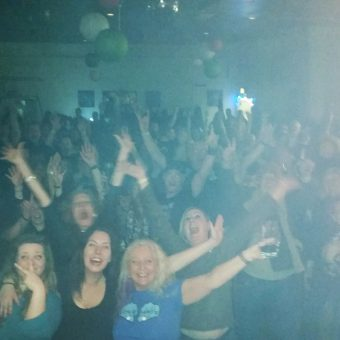 The crowd at Bretton Motorcycles Charity Christmas Bash, cheering and waving their arms.