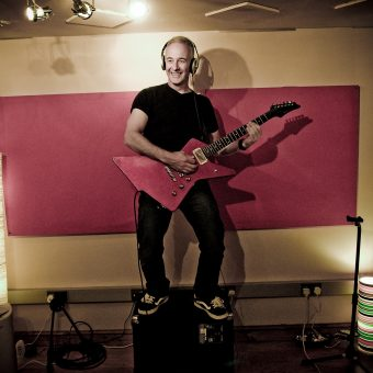 Neil standing on top of his amp at the studio, in colour.