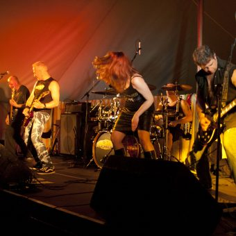 The band performing on stage, Ann head-banging.
