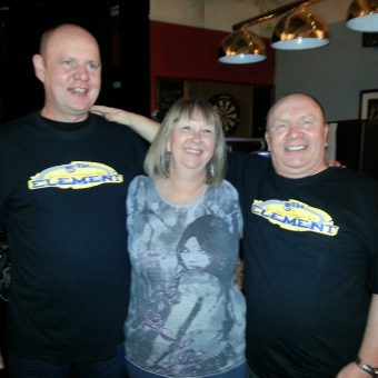 2 men wearing 5th Element band t-shirts standing either side of a lady.