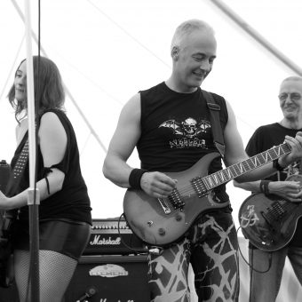 Ann, Neil and Rocker all playing guitars and smiling, black and white.