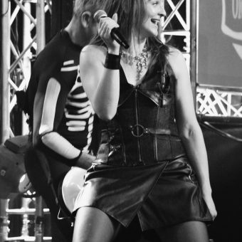 Ann smiling and holding her mic, Alan playing guitar behind her. Black and white.