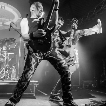 Neil raising his guitar, with Alan also raising his guitar and high-kicking behind him. Black and white.