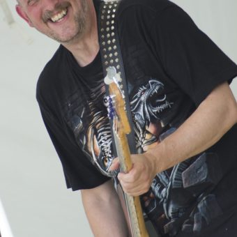 Richard playing bass and smiling.