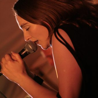 Close up of Ann singing intently on the mic.
