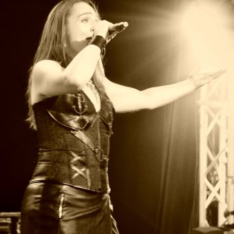 Ann singing, holding her mic in her right hand with her left arm held wide. Black and white.