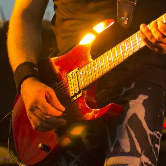 Close up of Neil playing his red Ibanez.