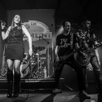 Ann, Dave and Alan performing on stage, black and white.