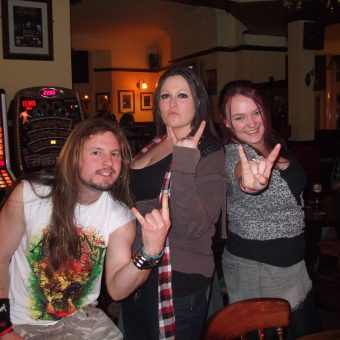 A young man with a beard and long hair and 2 young girls posing and giving the sign of the horns.