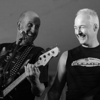 Richard and Neil on stage grinning. Black and white.