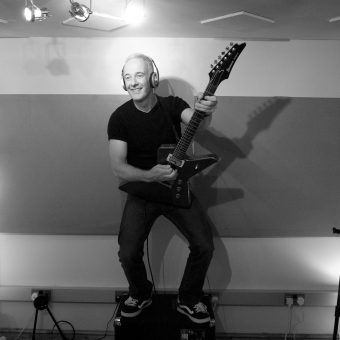 Neil standing on top of his amp at the studio, black and white.