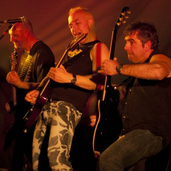 Richard, Neil and Alan playing their guitars and throwing shapes.