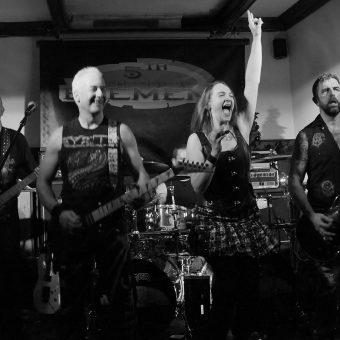 The whole band performing on stage, Ann with her right hand raised. Black and white.