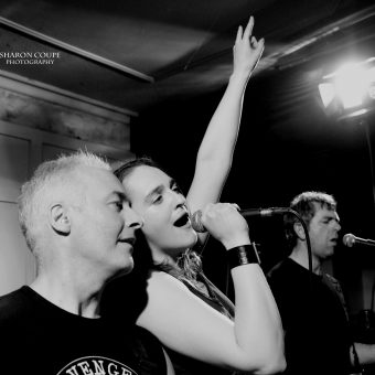 Neil, Ann and Alan singing, Ann with her hand raised in the sign of the horns. Black and white.