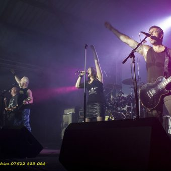 The band performing on stage, arms raised.