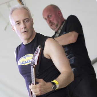 Neil and Richard playing on stage, Richard pulling a funny face.