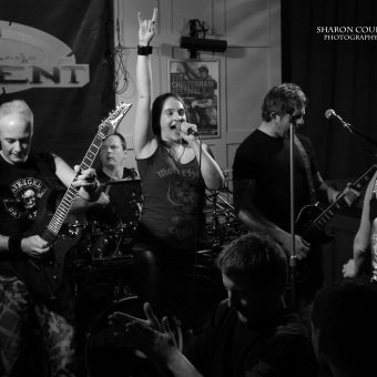 The band playing, Ann raising her hand with the sign of the horns, black and white.