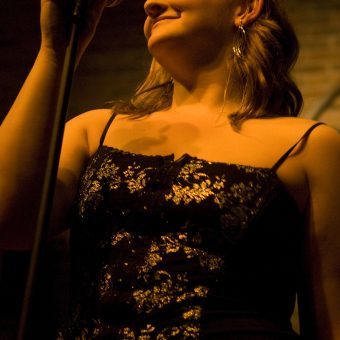 Ann smiling on the mic, in colour.