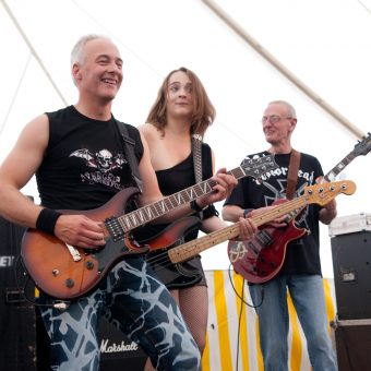 Neil, Ann and Rocker, all with guitars, smiling (colour).
