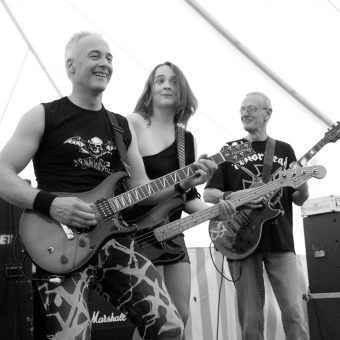 Neil, Ann and Rocker performing on stage. Black and white.