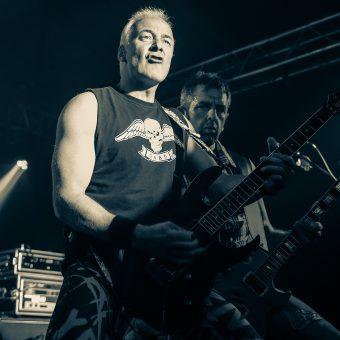 Neil gurning and playing guitar, Alan playing guitar behind him. Black and white.