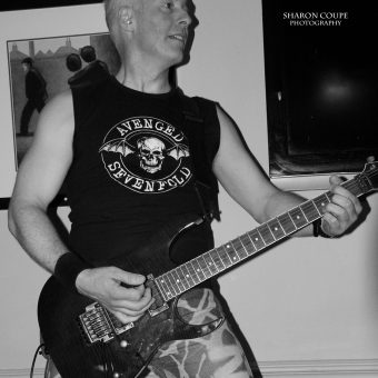 Neil playing guitar, standing on a chair, black and white.