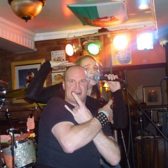 A man (Colin) giving the sign of the horns with crossed arms while Ann sings behind him and pats him on the head.