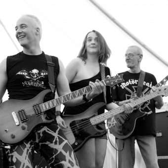 Neil, Ann and Rocker, all with guitars, smiling (black and white).