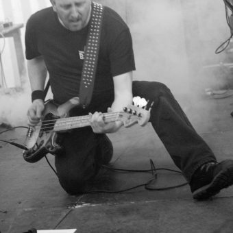 Richard playing bass on one knee. Black and white.