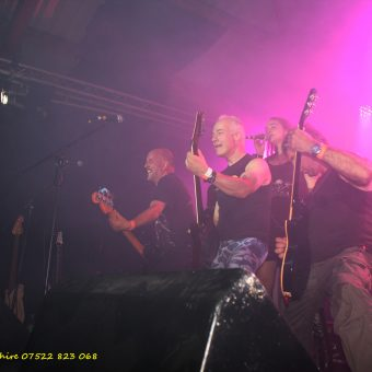 Richard, Neil, Alan and Ann throwing shapes at the front of the stage.